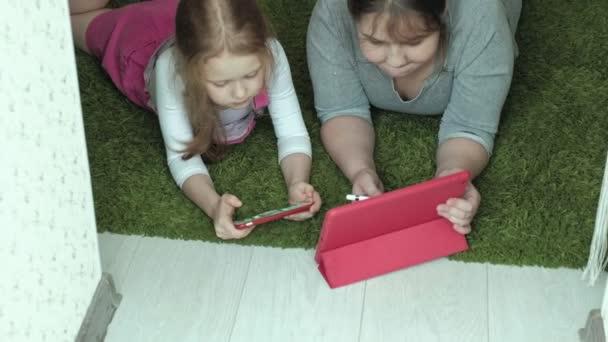 holky sestry hrát na tabletu v místnosti, surfování po webu, odpočinek