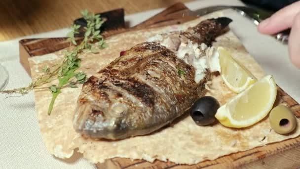 pořizování makrosnímků: grilované ryby dorylo s olivami a plátkem citronu na pita chléb.