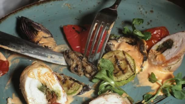 close-up shooting: chicken baked in bacon with vegetables, with sauce and green salad on a blue plate