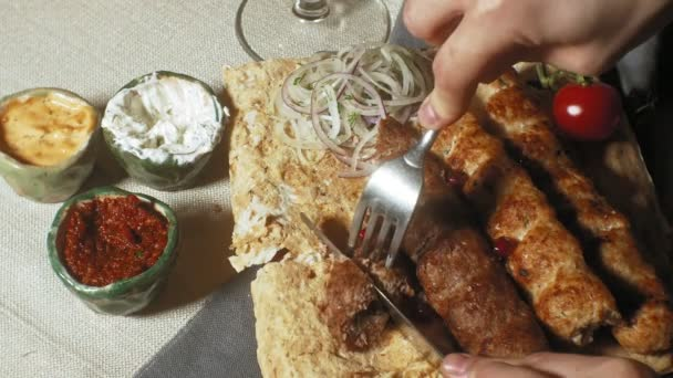 close-up shooting: grilled meat, kebab with vegetables and various sauces.