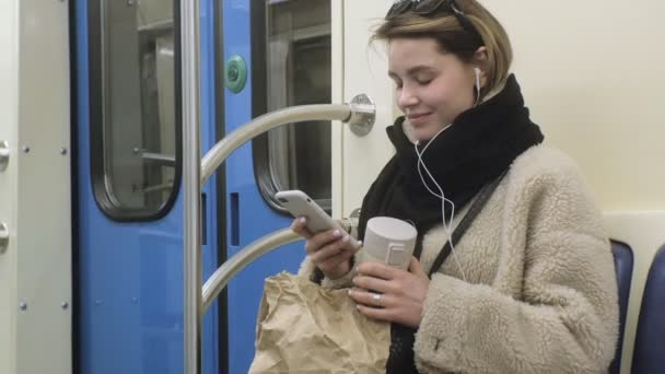 young brunette woman rides on public transport, uses the phone with headphones