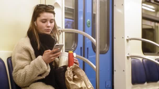 fiatal barna nő lovagol a tömegközlekedés, használja a telefont fejhallgatóval