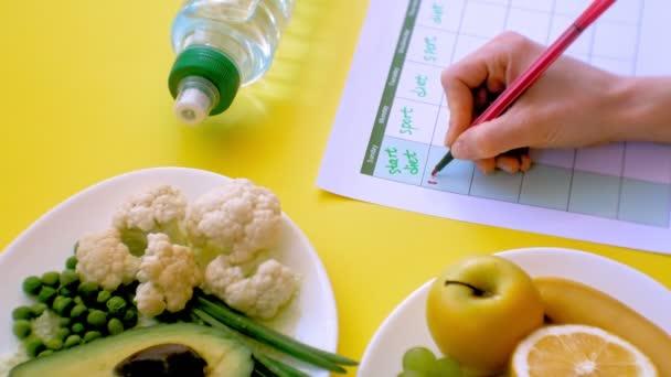 Fitness-Kalender halten. Konzept der gesunden Ernährung, Ernährung, Draufsicht, gelber Hintergrund