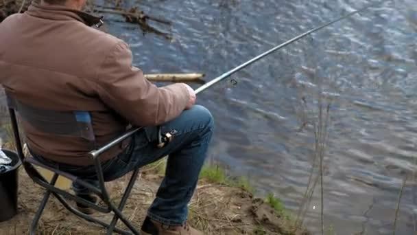 Érett ember fogások halat a folyón.