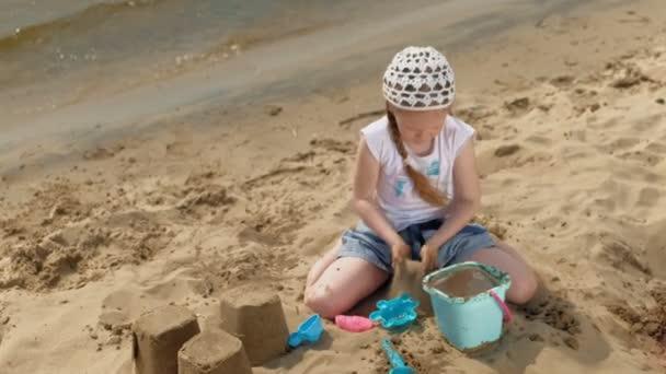Děti, které si za slunečného dne hrají na pláži u řeky