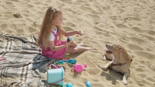 Mädchen isst Eis und füttert Hund im Freien.