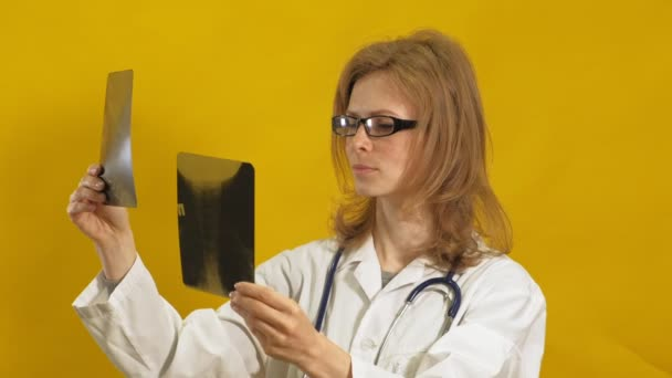 Young woman doctor. Yellow background. The concept of medicine.