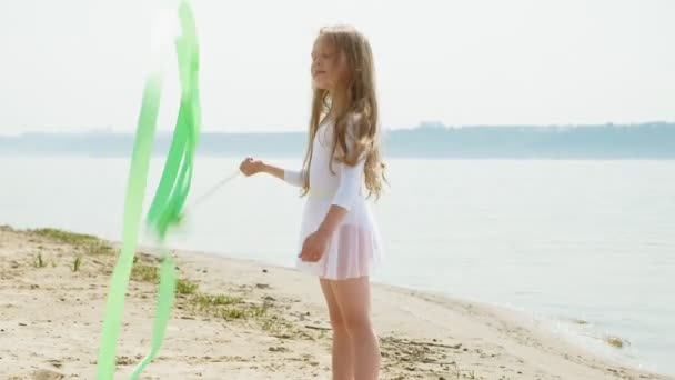 předškolní dívka s tancuje gymnastickou stuhu na písečné pláži. Léto, svítání