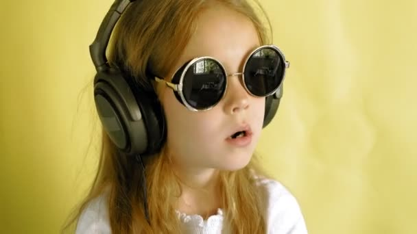 Veselá holčička ve sluchátkách na žlutém pozadí. Closeup portrét.