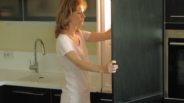 Mladá žena otevře lednici a vybere si produkty. Ráno