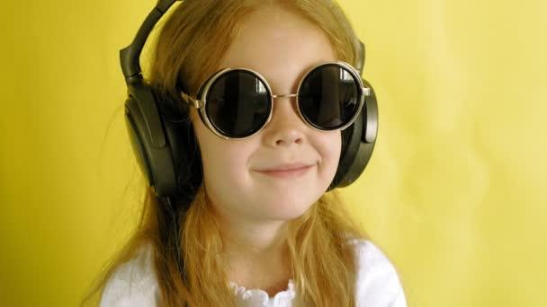 fröhliches kleines Mädchen mit Kopfhörern auf gelbem Hintergrund. Nahaufnahme-Porträt.