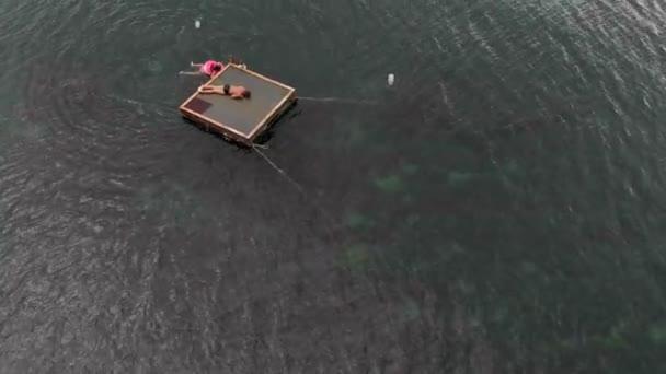 Fröhliche Kinder springen von einem Floß ins Meer. Luftaufnahme