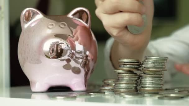 Lány preschooler tesz pénzt egy malacka bank rózsaszín disznó