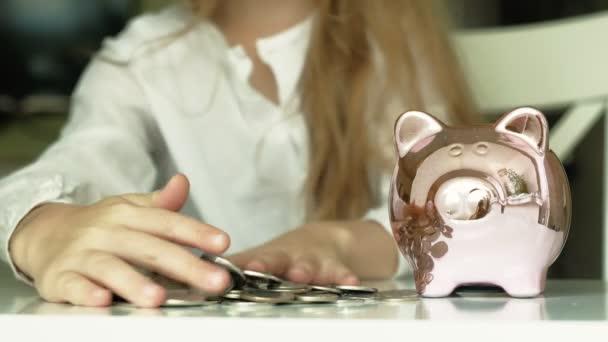 Girl preschooler puts money in a piggy bank pink pig