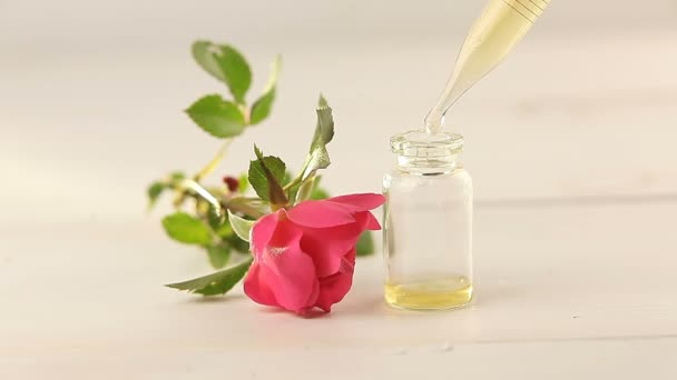 Essence of rose on White background in beautiful glass bottle