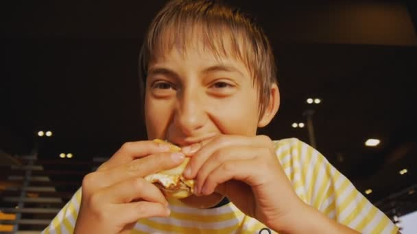 Teenager essen Fastfood. Nahaufnahme von hungrigem Teenie-Jungen, der in Fast-Food-Restaurant in Cheeseburger beißt.
