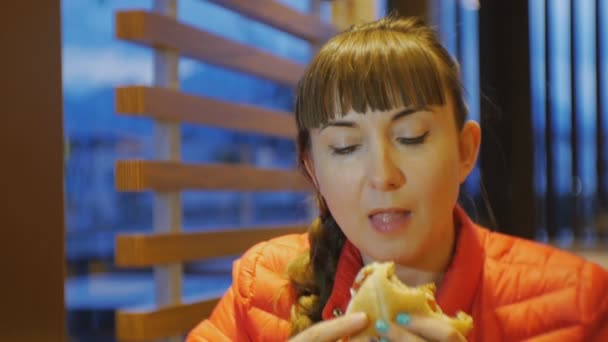 Woman eating fastfood. Close-up shot of attractive female biting and chewing cheeseburger in fast food restaurant.