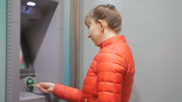 Woman using cash machine. Attractive young female in red bubble jacket inserting credit card into ATM and entering pin code.
