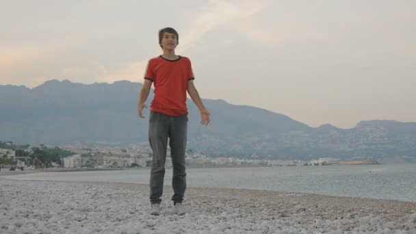 Teenager playing flying disc. Caucasian teen boy catching flying disk on a empty low season beach on mountain seashore background.