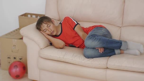 Teenager auf Schlafcouch. Kaukasische teenboy im roten T-shirt und Blue  Jeans schlafen auf beigem Ledersofa auf Boxen und Fußball Ball Hintergrund  bewegen. Umzug in ein neues Hotel-Konzept.