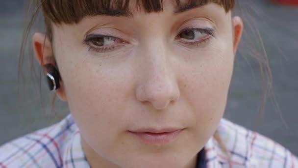 Detail atraktivní kavkazské ženy mluví po telefonu přes bezdrátové sluchátka s mikrofonem venku.