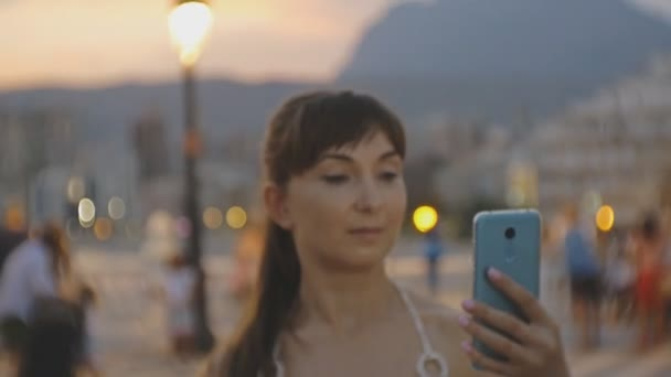 Attractive young female using smartphone. Caucasian woman looking at phone screen on sunset mountain resort city lights background.