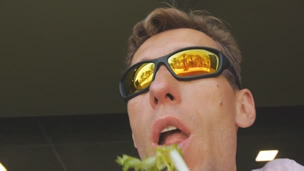 Man eating fastfood. Close-up shot of caucasian male in mirror sunglasses reflecting palm tree beach eating salad with a plastic fork in fast food restaurant.
