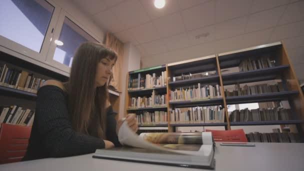 Mladá žena Kavkazský listoval ilustrovanou knihu v knihovně.