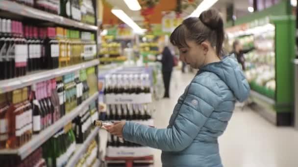 Žena v supermarketu. Mladá žena Kavkazský v modré bundě čtení štítku na láhve volba bílé šumivé víno.