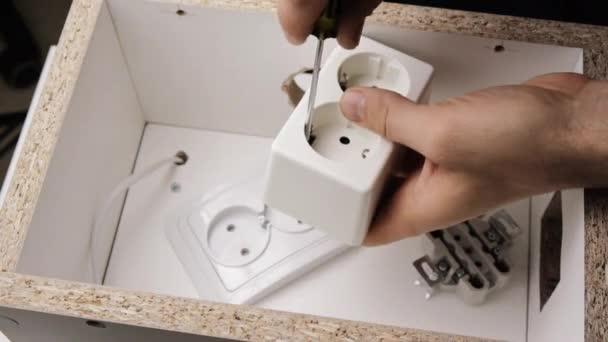 Detail mužských rukou opravy bílé zásuvky s šroubovák.
