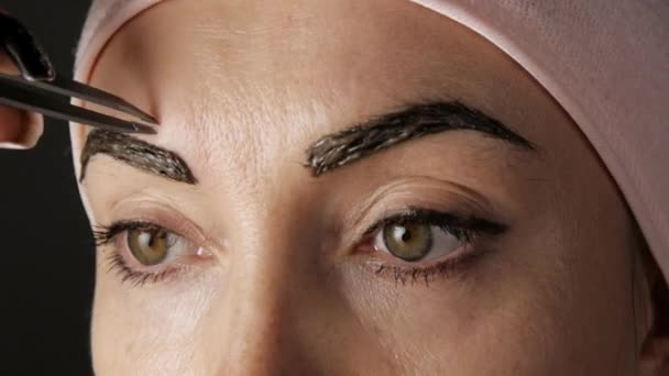 Eyebrows care. Attractive woman getting her eyebrows threaded. Close-up.