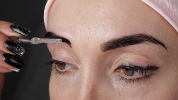 Dyeing of eyebrows. Close-up of woman combing her eyebrows.