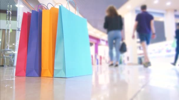 Barva balíčky pro nakupování v nákupním středisku na pozadí lidí