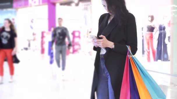 Dívka používá smartphone s barevných tašek pro nakupování v nákupním středisku
