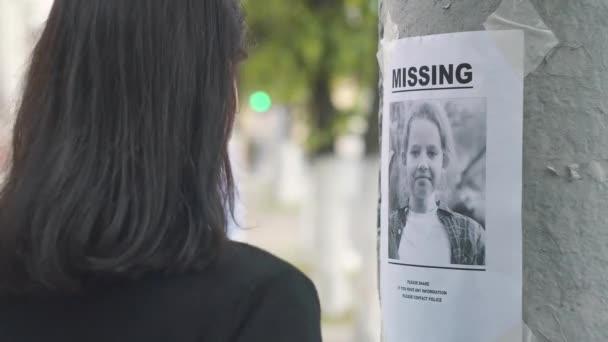 Dívka dobrovolníků hole letáky o ztrátě dítěte, zblízka