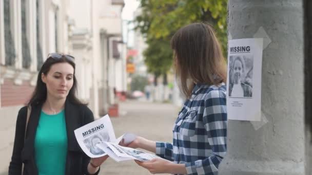 Ragazza di volontariato distribuendo opuscoli sul bambino scomparso