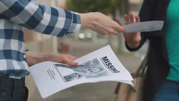 Ragazza distribuendo opuscoli sul bambino scomparso, primi piani
