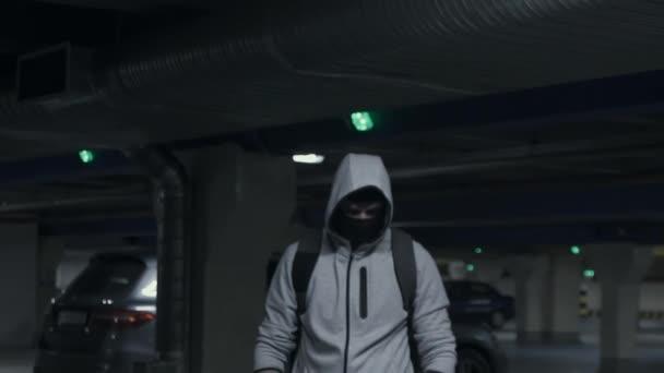 Muž zločinec v kuklu a kapuce, při pohledu na fotoaparát v podzemních parkovištích, pomalé mo