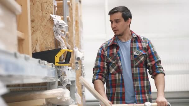 man in a plaid shirt in ain Department store buys a saw