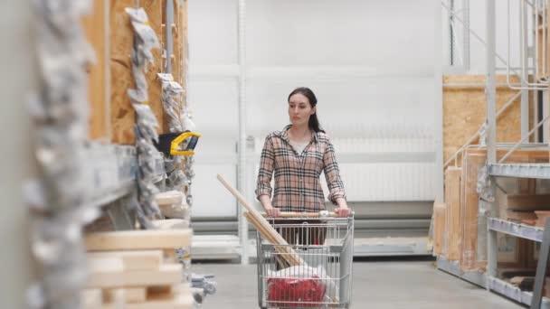 dívka v kostkované košili v železářství s vozíkem koupí pila