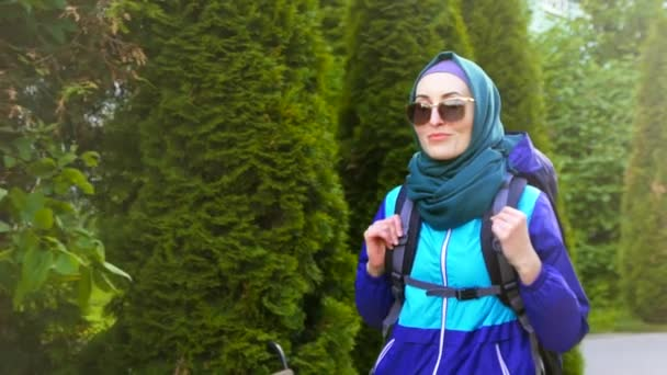 portrait of a beautiful Muslim woman in hijab tourist with a backpack in glasses uses talking and smiling