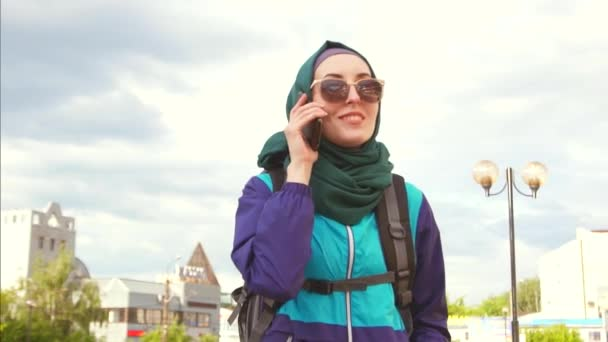 a girl tourist in a headscarf and sunglasses in a backpack talking on the phone