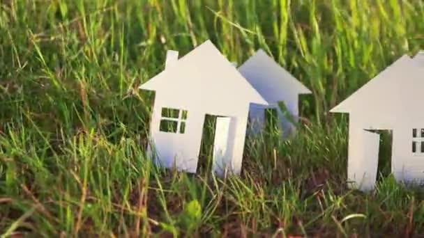 více kartónové house z papíru na zelené trávě pozadí