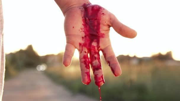 mužské ruky s níž vytéká krev, před západem slunce, koncepce dopravní nehody