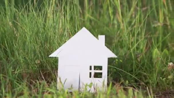 Kartónové house z papíru na pozadí zelené trávy