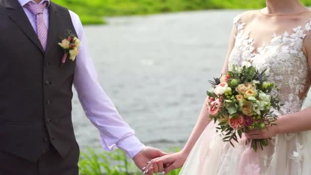 newlyweds on the background of the river holding hands, beautiful brides dress