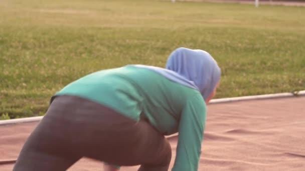 Muslimská dívka sportovec v hidžábu na startovních bloků, pomalé mo