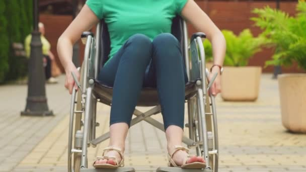Portrait of an attractive disabled girl in a wheelchair looking at the camera,slow mo