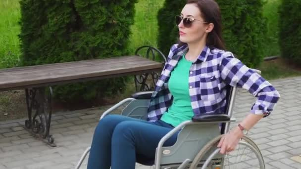Attractive disabled girl in a shirt and glasses on a wheelchair rides in the Park