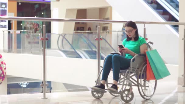 A disabled woman in a wheelchair using the phone in the Mall after shopping